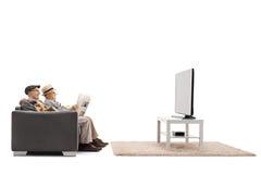 Mayores que ven la TV y que leen un periódico foto de archivo libre de regalías