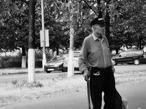 Mayores rusos - viejo hombre mal vestido con un bastón que camina Foto de archivo