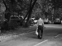 Mayores rusos - viejo hombre solo mal vestido con un bastón que camina Fotos de archivo libres de regalías