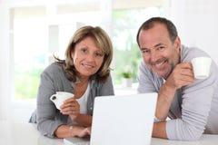 Mayores sonrientes que beben el café usando el ordenador portátil Imagen de archivo libre de regalías