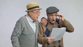 Mayores sorprendidos que miran documentos con incredulidad metrajes