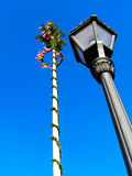 Maypole. Big decorated maypole and black lamp pointing to the sky Royalty Free Stock Photo