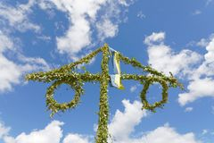 Maypole made of green leaf and the blue sky and some white cloud Stock Photos