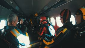 Group of skydivers sits inside a small plane awaiting a jump. Slow Motion stock footage
