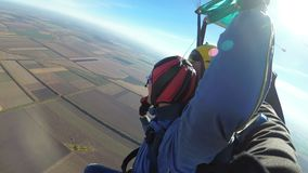 Skydivers flying in tandem under the open parachute. Mayskoe, Dnepr, Oktober 14, 2018: Skydivers flying in tandem under the open parachute. Instructor teaches a stock video