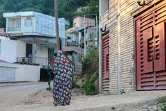 Mazandaran, der Iran - 19. Juli 2017: Iranische Frau mit traditionellem buntem burka in einem ländlichen Gebiet vom Iran gehend i stockbild