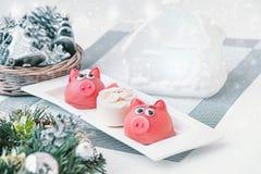 Mazapán en la forma del símbolo del rosa del Año Nuevo - cerdo, macarrones delicados dulces, melcochas, cacahuetes en pastel del  foto de archivo libre de regalías