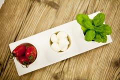 Mazarella saboroso e manjericão dos tomates na placa na tabela Imagens de Stock