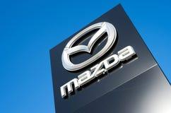 Mazda återförsäljaretecken mot blå himmel Arkivfoton