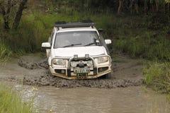 Mazda blanc BT-50 4x4 3L croisant l'étang boueux Image libre de droits