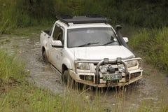 Mazda blanc BT-50 4x4 3L croisant l'étang boueux Images stock