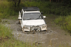 Mazda blanc BT-50 4x4 3L croisant l'étang boueux Photo stock