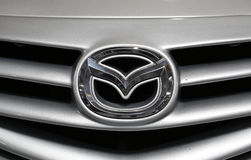 Mazda metallisk logocloseup på den Mazda bilen Arkivfoto