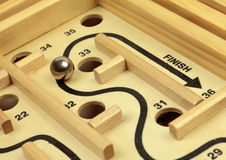 Maze and Ball Game. Detail of wooden maze dexterity game with ball nearing finish Royalty Free Stock Photography