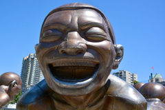 A-maze-ing Laughter. VANCOUVER BC CANADA JUNE 15 2015: A-maze-ing Laughter is a 2009 bronze sculpture by Yue Minjun, located in Morton Park in Vancouver, British royalty free stock image
