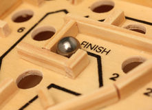 Maze Puzzle. Detail of dexterity maze game with ball at finish Royalty Free Stock Photography