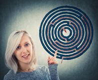 Maze solution. Close up portrait of smiling woman pointing her finger up showing a solved maze sketch. Young businesswoman find the solution of a round labyrinth Stock Photography