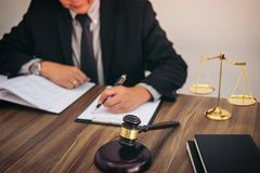 Mazo en la tabla de madera y abogado o juez que trabajan con el acuerdo fotografía de archivo libre de regalías