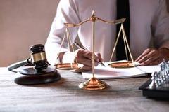 Mazo en la tabla de madera y abogado o juez que trabajan con el acuerdo en tema de la sala de tribunal, concepto de la justicia y imágenes de archivo libres de regalías