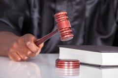 Mazo llamativo de la mano en una sala de tribunal Imagen de archivo libre de regalías