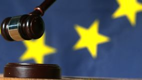 Mazo que cae sobre bloque del sonido con la bandera de unión europea en fondo metrajes
