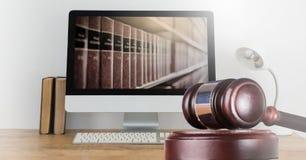 Mazo y ordenador con los libros de la ley y de la justicia fotos de archivo