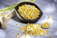 Mazorca y granos amarillos del maíz en pote de arcilla en el zea de madera blanco mayos del fondo fotos de archivo