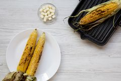 Mazorcas de maíz asadas a la parrilla en el asado a la parilla de la cacerola y de la placa blanca, mantequilla, visión superior  fotos de archivo libres de regalías