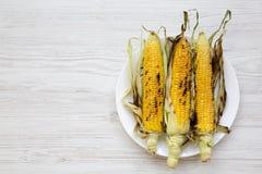 Mazorcas de maíz asadas a la parrilla en una placa redonda sobre la superficie de madera blanca, visión superior Desde arriba de, fotos de archivo libres de regalías