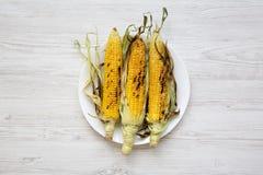 Mazorcas de maíz asadas a la parrilla sabrosas en una placa redonda sobre el fondo de madera blanco, visión superior foto de archivo