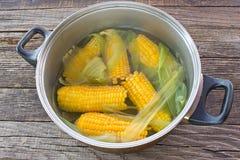 Mazorcas de maíz cocinadas en pote en la tabla de madera fotografía de archivo