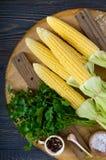 Mazorcas de maíz jovenes con las hojas, especias, hierbas, sal del mar fotos de archivo libres de regalías