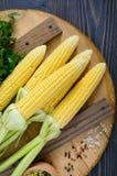 Mazorcas de maíz jovenes con las hojas, especias, hierbas, sal del mar en una bandeja de madera fotografía de archivo