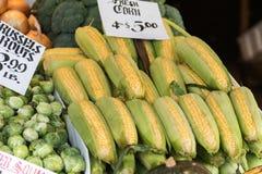 Mazorcas de maíz y coles de Bruselas en una parada en el mercado de lugar de Pike de Seattle fotografía de archivo libre de regalías