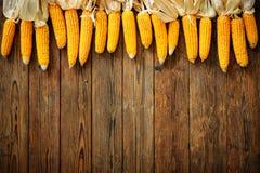 Mazorcas de maíz en fondo de madera rústico Foto de archivo
