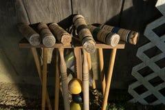 Mazos de croquet bien-usados viejos en un estante que se inclina contra una pared de madera, a un ángulo hacia abajo foto de archivo libre de regalías