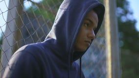 Mazza da baseball afroamericana della tenuta dell'adolescente, banda giovanile in ghetto, primo piano archivi video