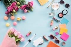 Mazzi dei fiori con gli occhiali da sole ed i cosmetici con il modello dei maccheroni Immagini Stock