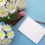Mazzi dei fiori del sapone, blocco note in bianco con la matita, libri su fondo blu-chiaro immagine stock libera da diritti