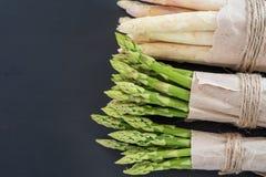 Mazzi di asparago verde e bianco su una vista superiore del fondo di legno scuro Fotografia Stock Libera da Diritti