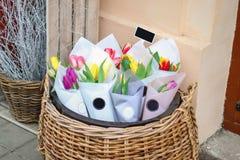 Mazzi di colore dei fiori in un canestro accanto ad un caffè moderno fotografia stock libera da diritti