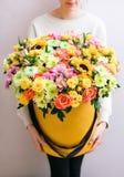 Mazzi di lusso dei fiori misti nel contenitore di cappello rose nelle donne delle mani Immagini Stock Libere da Diritti