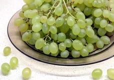Mazzi di uva verde matura in piatto trasparente sul primo piano del tavolo da cucina Immagine Stock