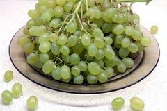 Mazzi di uva verde matura in piatto trasparente sul primo piano del tavolo da cucina Fotografie Stock Libere da Diritti