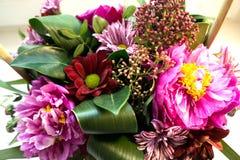 Mazzo adorabile dei fiori in tonalità viola in un canestro wattled fotografie stock libere da diritti