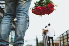 Mazzo affranto della tenuta dell'uomo delle rose rosse che ritengono triste mentre s Fotografia Stock