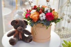 Mazzo alla moda dei fiori in un contenitore beige di cappello immagini stock libere da diritti
