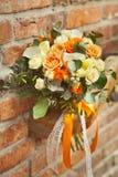 Mazzo arancio di nozze su un fondo del mattone fotografie stock