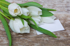 Mazzo bianco dei tulipani e cartolina d'auguri in bianco Fotografia Stock