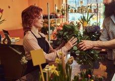 Mazzo d'acquisto maschio barbuto dei fiori al negozio floreale Immagini Stock Libere da Diritti